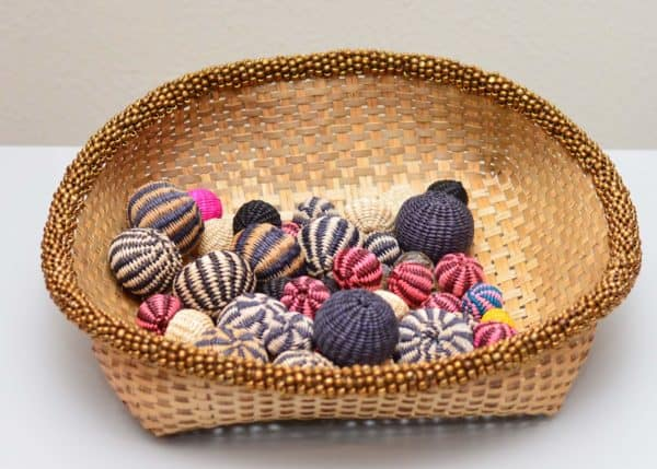 Picture of a Small Woven Basket in Iraca with Brown Metallic Beaded Border holding various Colorful decorative balls made from iraca