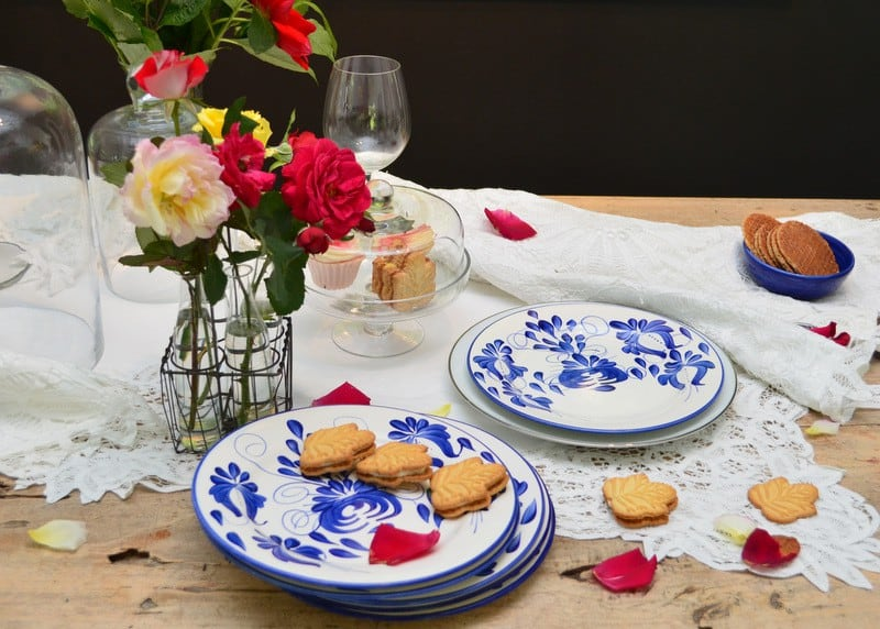 Picture of hand painted ceramic dinner plates with cookies and flower petals on top