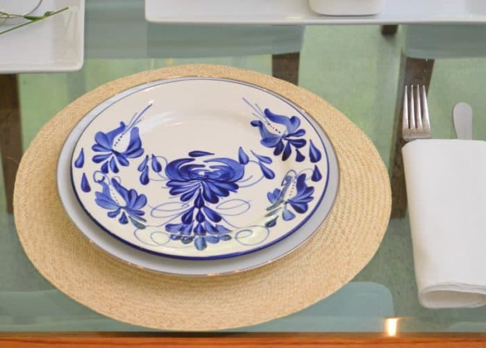 Close up picture of hand painted 10 inch dinner plates on top of round placemats made of iraca fibers sitting on a glass dining table