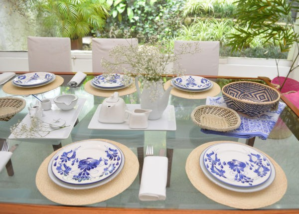 Picture of hand painted dinner plates on top of round placemats made of iraca in a beautifully decorated dinning table