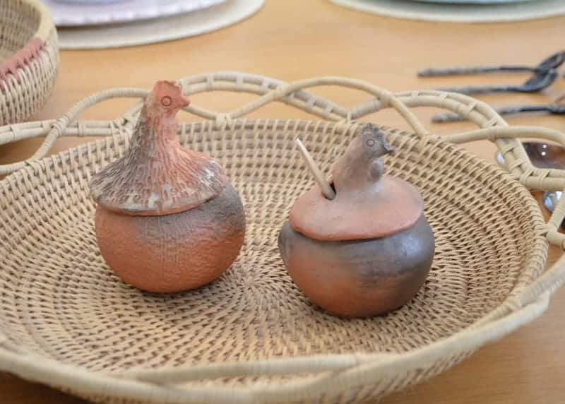 Picture of two clay condiment serving hens sitting on top of a Round Serving Tray with Handles made of Mamure