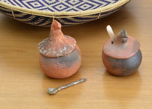 Picture of two clay condiment serving bowls in the form of chickens sitting on a table next to a mother of pearl tiny teaspoon and a colorful flat basket