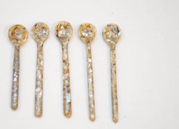 Close up picture of five tea spoons hand carved from mother of pearl