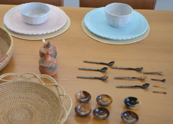 Picture of small condiment bowls made from horn next to teaspoons made from horn and mother of pearl sitting on a table with plates and trays