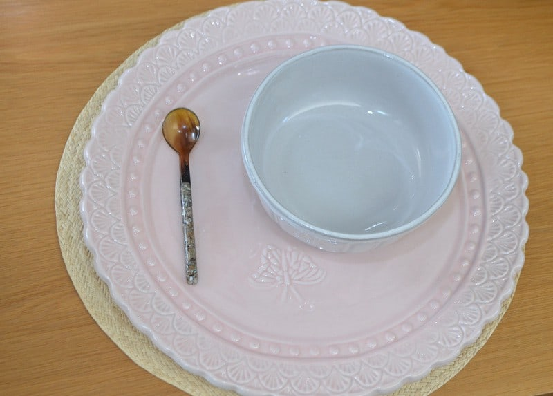 Picture of small teaspoon made from horn and mother of pearl on plate next to bowl