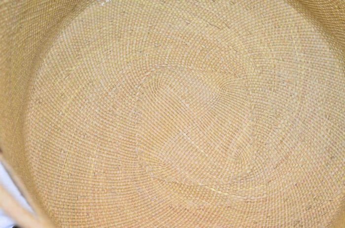 Close Up Product Image Inside a Large Woven Basket with Handles in Tan Iraca with Blue and White Stripe Pattern