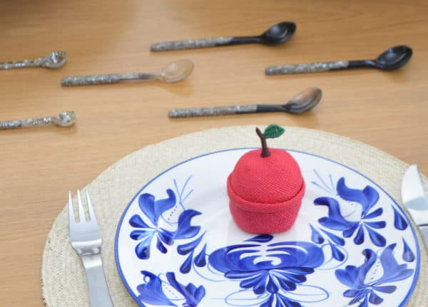 Picture of a hand painted dinner plate with a small woven basket in the form of an apple made from iraca, sitting on top of an iraca round placemat and next two various small teaspoons made from horn and mother of pearl