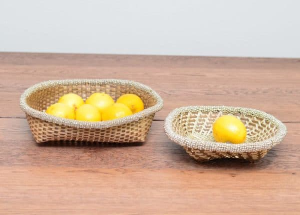 Picture of two Iraca small woven baskets holding lemons sitting on a wooden dinning table