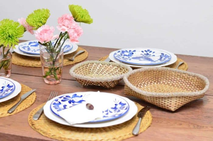 Picture of dinning table decorated with fresh flower, hand painted ceramic dinner plates, hand woven placemats made from esparto fibers, and small woven baskets from iraca with white beaded borders