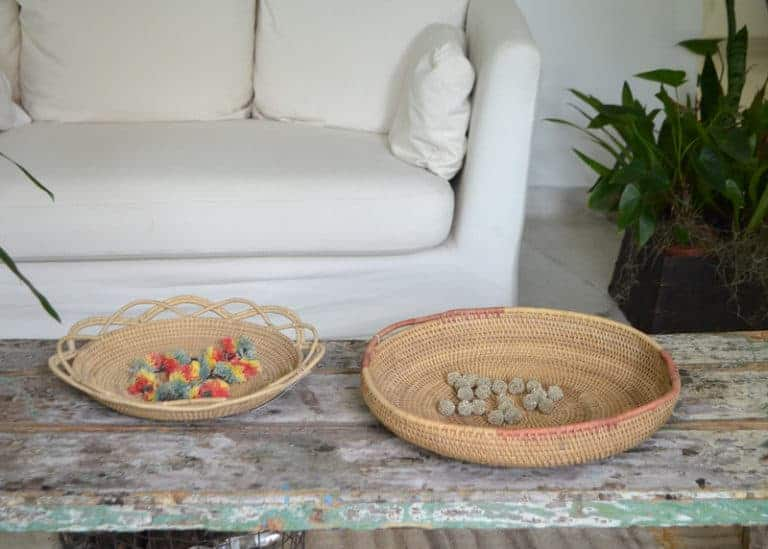 Picture of a Round Serving Tray with Handles and a decorative shallow bowl hand woven from Mamure natural fibers, sitting on a shabby chick centerpiece table