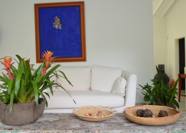 Picture of a Round Serving Tray with Handles and a decorative shallow bowl hand woven from Mamure natural fibers, sitting on a shabby chick centerpiece table next to a planter with tropical flowers and with a white sofa and blue painting in the background