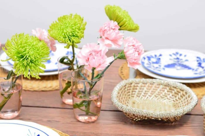 Picture of dinning table decorated with fresh flowers, hand painted ceramic dinner plates, hand woven placemats made from esparto fibers, and a small woven basket from iraca with white beaded borders.