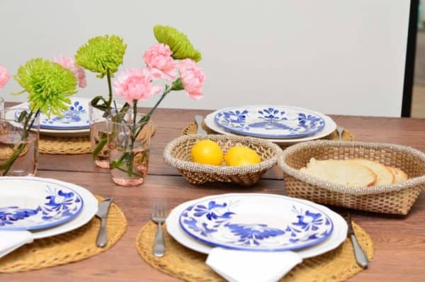 Picture of dinning table decorated with fresh flowers, hand painted ceramic dinner plates, hand woven placemats made from esparto fibers, and small woven baskets from iraca with white beaded borders holding lemons and bread.