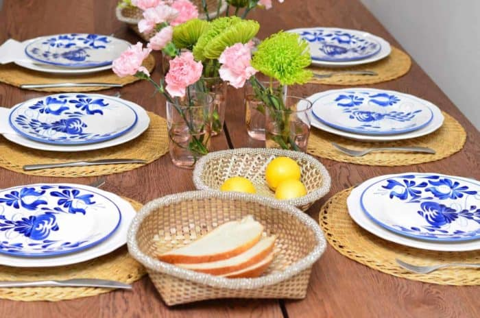 Picture of hand painted ceramic dinner plates on top of natural placemats made of esparto and bread baskets made of iraca with beaded border in a dinning table setting