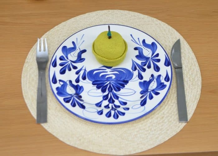 picture of an apple shaped little basket sitting on a hand painted plate placed on top of an iraca woven placemat