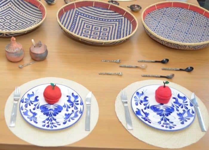picture of dinning table decorated with red apple shaped small baskets, iraca placemats, hand painted plates, chicken Condiment Serving Bowls, horn and mother of pearl teaspoons and flat baskets