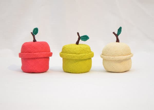Picture of three small woven apple-shaped baskets in red, yellow and white iraca fibers with lids on