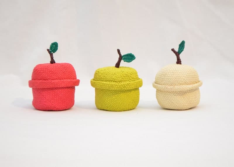 Picture of three small woven apple-shaped baskets in red, yellow and white iraca fibers