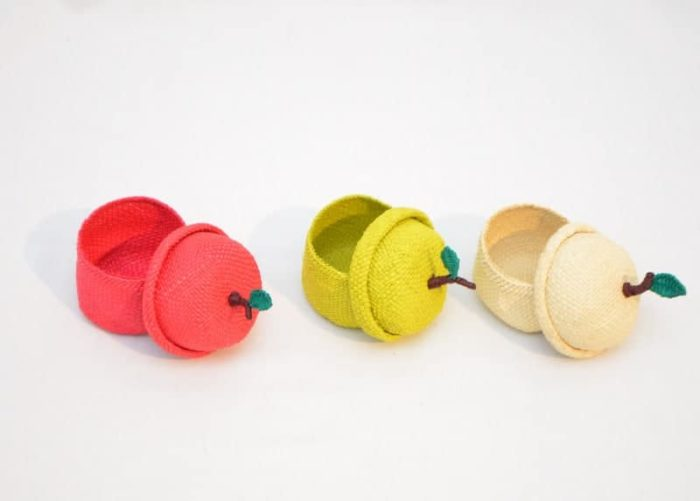 main product image of three apple shaped tiny baskets in red, green and white with lids lying on the side