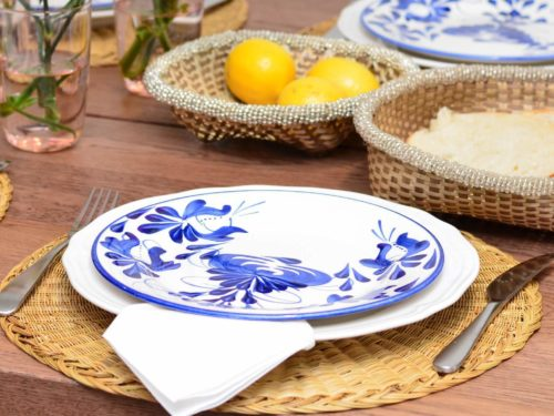 Close up picture of hand painted ceramic dinner plates on top of natural placemats made of esparto