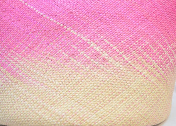 Closeup picture of a large pink woven basket showing the detail of Iraca weaving by women from Sandona, Nariño - Colombia
