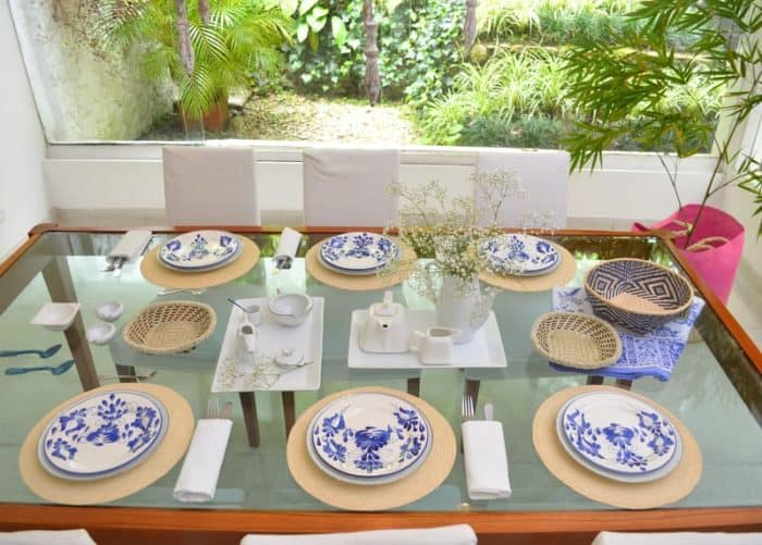 Picture of a glass top dining table set up with six round woven placemats made from iraca, six hand painted ceramic plates, two small woven baskets with beaded border, one small woven basket in paja tetera and an extra large pink round woven basket made from iraca being used as a planter