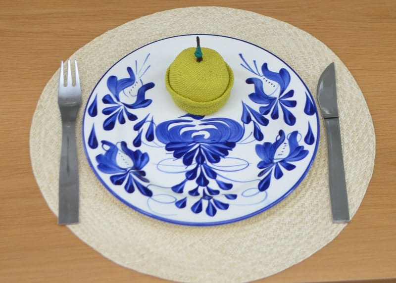 Close up picture of hand painted ceramic dinner plates on top of round placemats made of iraca fibers with an Apple Shaped tiny Woven Baskets in Iraca
