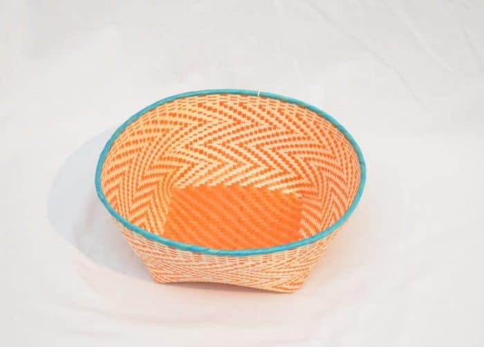 Main product image from the top of a small woven basket made from paja tetera fibers with aqua colored border,and orange pattern