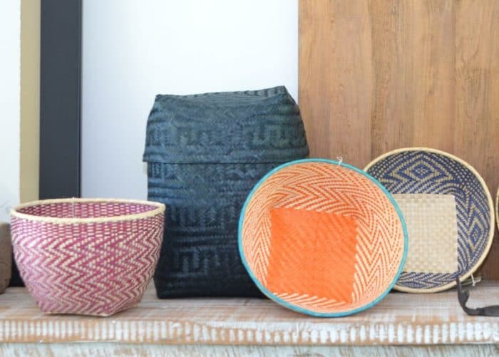 Picture of three colorful small woven baskets and blue rectangular woven basket with lid made from papa tetera natural fibers sitting on a wooden table