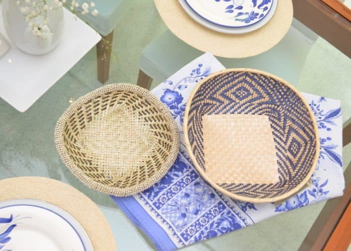 Picture of small woven basket with beautiful white and blue pattern sitting on a glass dining table next to a small woven basket made from iraca with beaded border