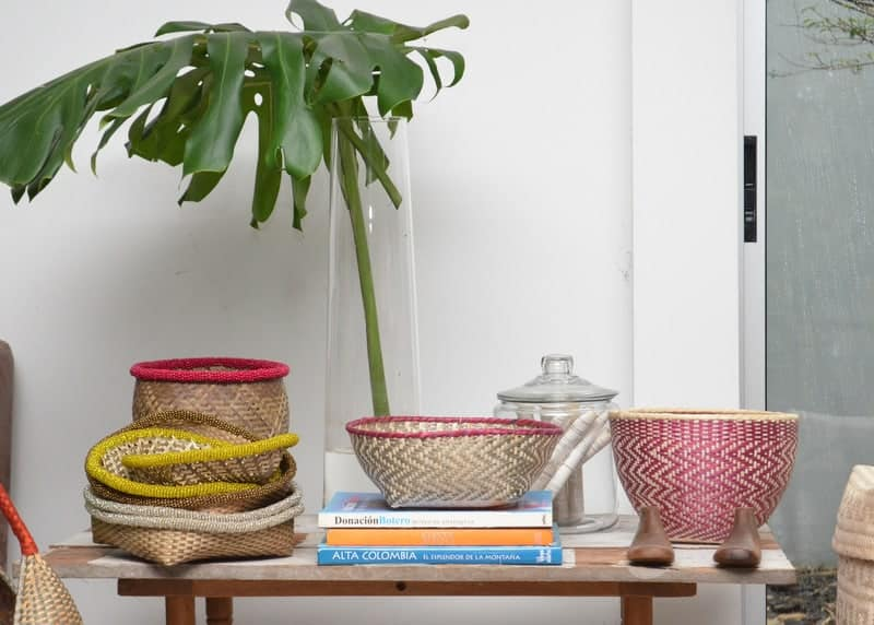 Picture of various bread baskets made of iraca and a tall glass vase with a balazo leaf sitting on a side table