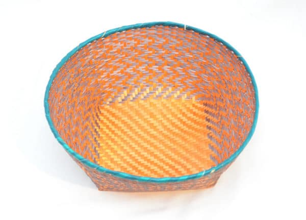 Main product image from the top of a small woven basket with border in aqua color, and orange and brown pattern walls