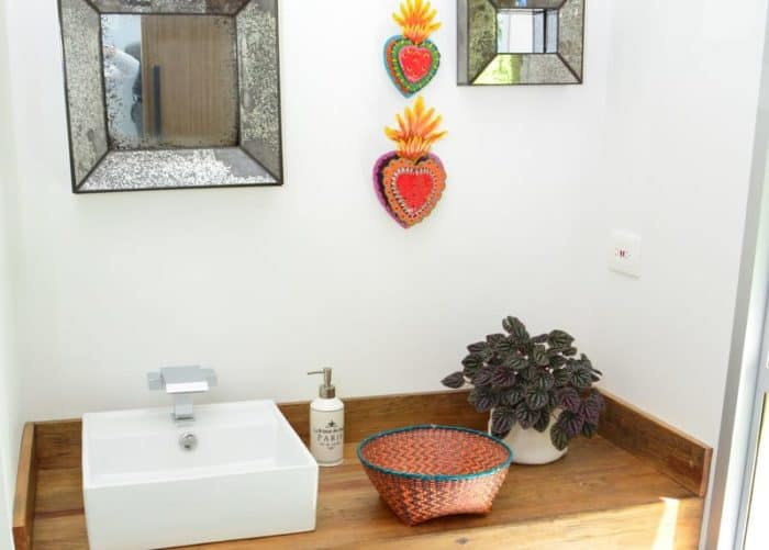 Picture of small woven basket with aqua border and orange and brown pattern wall on top of a bathroom countertop. Walls decorated with mexican hearts and mirrors.