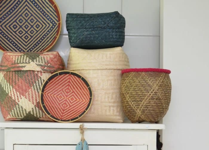 picture of two flat baskets (aka. balays), three rectangular woven baskets with lids and a round woven basket with beaded border stacked on top of a white drawer