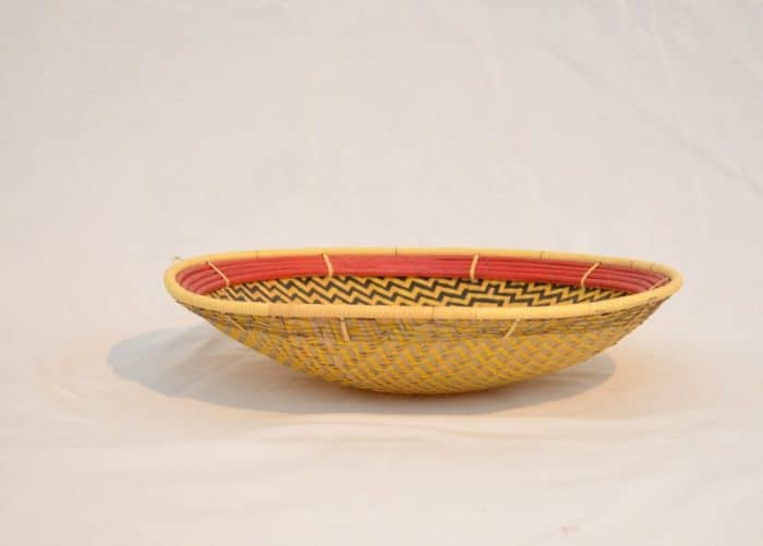 side view product image of a small flat basket (aka. Balay) with a Yellow and dark brown pattern that resembles a Spider Web and a red frame