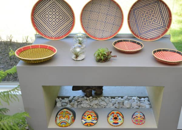 picture of various flat baskets with colorful patterns and four ceremonial masks on a large gas fireplace
