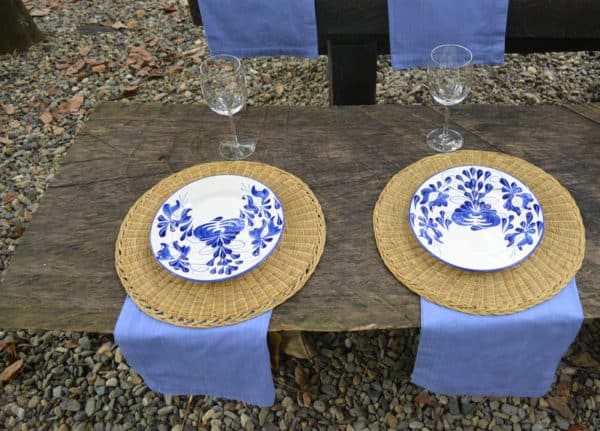 Picture of two hand painted ceramic dinner plates on top of two natural woven placemats made of esparto on a decorated outdoor picnic table setting