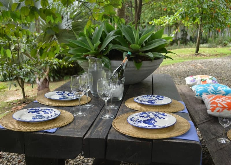 Picture of hand painted ceramic dinner plates on top of natural placemats made of esparto in a luxury decorated outdoor picnic table setting