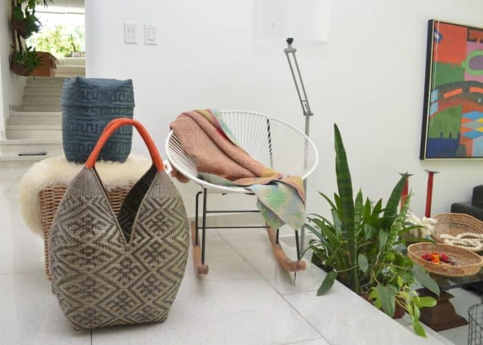 pciture of an Extra Large Cuatro Tetas basket and a blue paja tetera rectangular woven basket with lid featured in a living room next to a white rocking chair