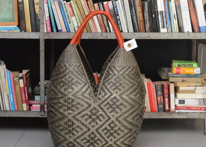 image of an Extra Large Cuatro Tetas basket in Brown Spider Pattern with Golden Orange Handles sitting in front of a rustic metallic bookshelf