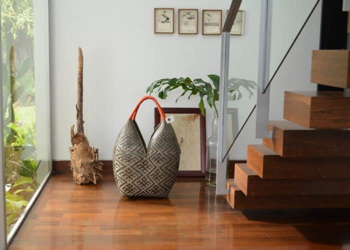 pciture of an Extra Large Decorative Basket (Cuatro Tetas) in Brown Spider Pattern with Golden Orange Handles sitting next to wooden stairs and decorative picture frames