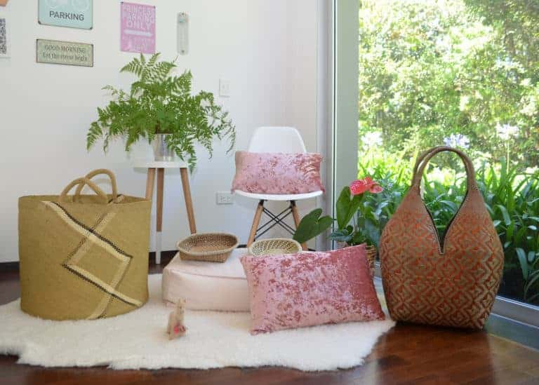 Picture of Large Woven Basket and two bread baskets made from iraca fibers, plus a large cuatro tetas basket in Golden Orange and Natural Green with Butterfly Pattern sitting next to pink decorative pillows in a bedroom setting