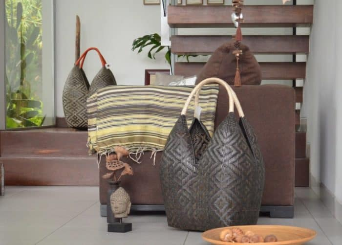 product image of a Cuatro Tetas Basket in Dark Brown Shrimp eye pattern and Beige Handles sitting on the floor of a living room next to a brown sofa