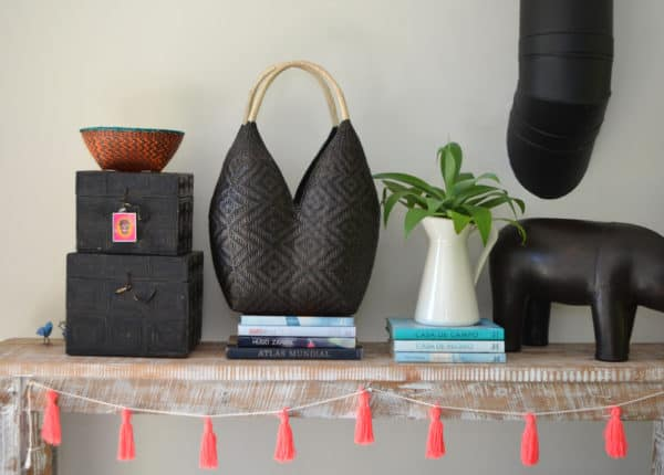 product image of a Cuatro Tetas Basket in a dark brown shrimp eye pattern with beige handles sitting on a shabby chick table