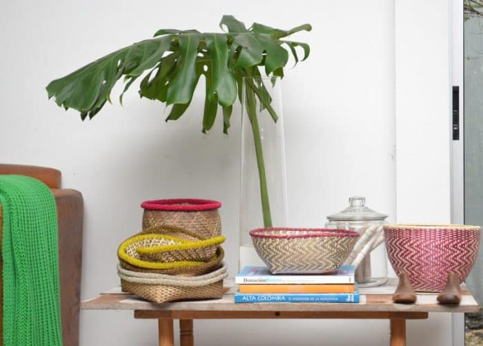 Picture of various Small Woven Baskets made from Iraca with Beaded Border and Paja Tetera sitting on a coffee table with a balazo leaf in a tall glass vase