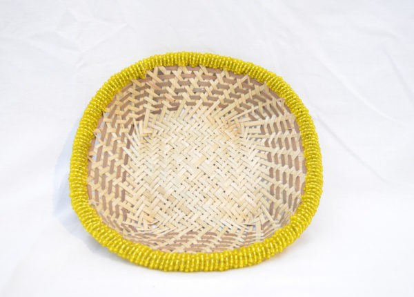 Main product image from the top of a small woven basket from iraca with yellow beaded border