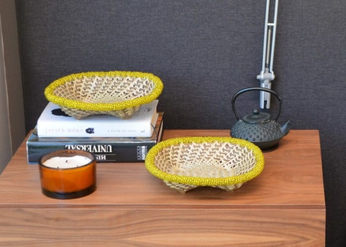 Picture of Two small woven baskets with yellow beading on a wooden night table