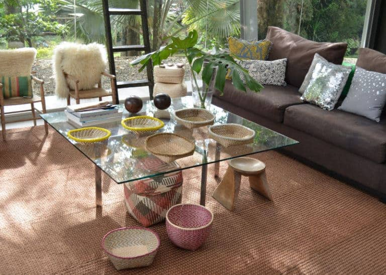 Picture of various small woven baskets made from iraca with beaded border sitting on a glass centerpiece table in a living room. Under the same table there are two more small woven baskets made from paja tetera and a rectangular woven basket with lid also made from paja tetera