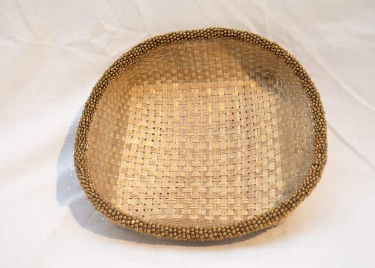 Main product image from the top of a small woven basket from iraca with brown metallic beaded border