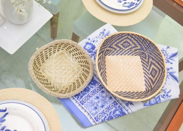 picture of two small woven baskets made from iraca with white beading and paja tetera sitting on a glass dining table